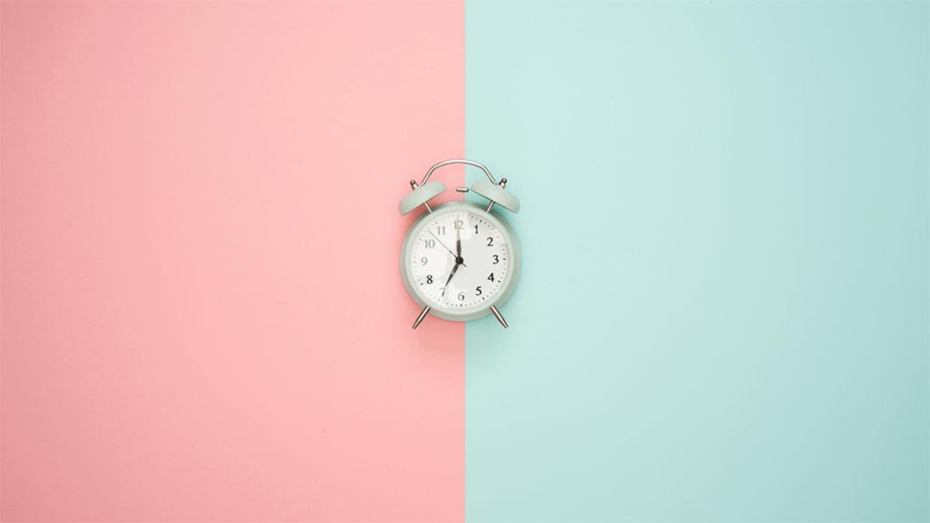 despertador clássico posicionado sobre um fundo rosa e verde