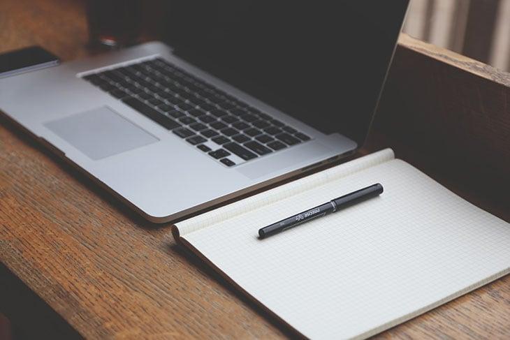 notebook com caderno de anotações ao lado